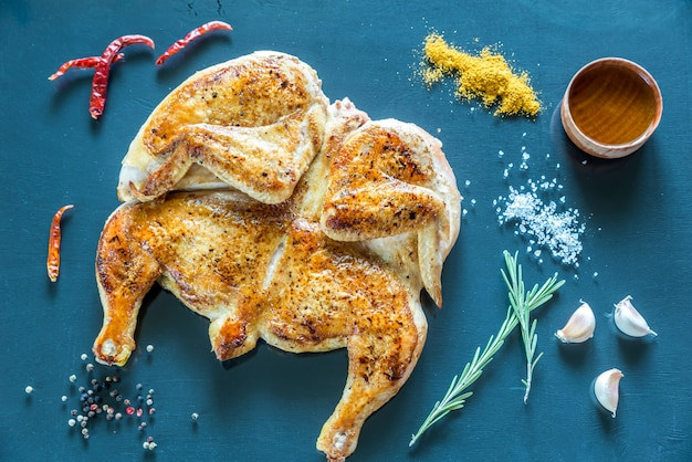 Gegrilde kip met ingrediënten op de donkere houten oppervlak