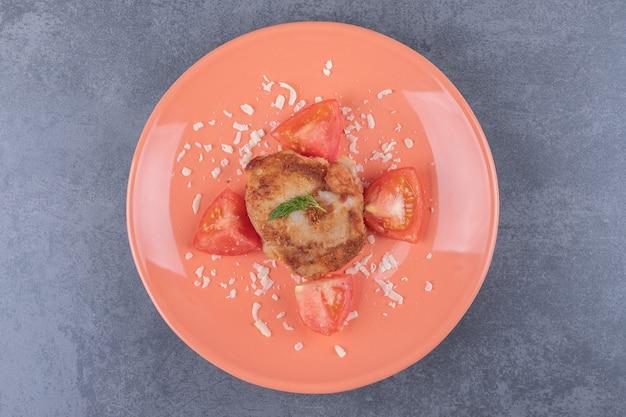 Gegrilde kip met plakjes tomaat op oranje plaat.