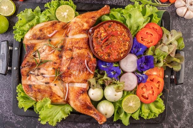 Gegrilde kip op een bord met chili pepers, knoflooksaus en besprenkeld met peper zaden.