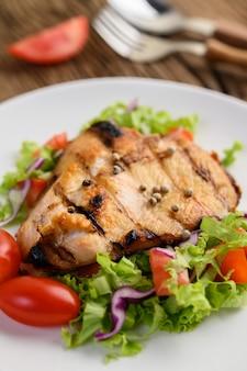 Gegrilde kip op een witte plaat met een salade van tomaten, wortelen en pepers in stukjes gesneden.