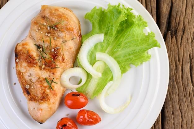 Gegrilde kip op een witte plaat met tomaten, salade en ui.