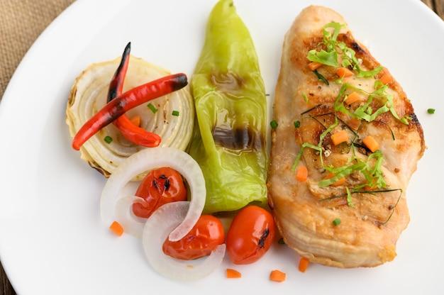 Gegrilde kip op een witte plaat met tomaten, salade, ui, chili en saus.