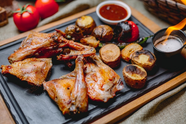 Gegrilde kip op houten bord aardappel tomaat peper chili saus zijaanzicht