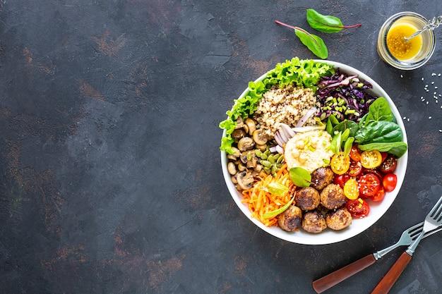 Gegrilde kip, rijst, pittige kikkererwten, avocado, kool, peper buddha bowl op donker, bovenaanzicht.