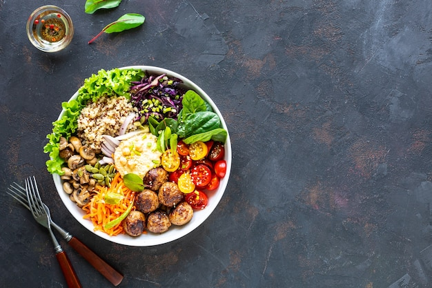 Gegrilde kip, rijst, pittige kikkererwten, avocado, kool, peper buddha bowl op donkere ondergrond, bovenaanzicht. heerlijk uitgebalanceerd voedselconcept