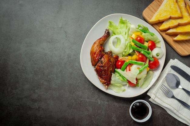 Gegrilde kip steak en groenten op donkere achtergrond