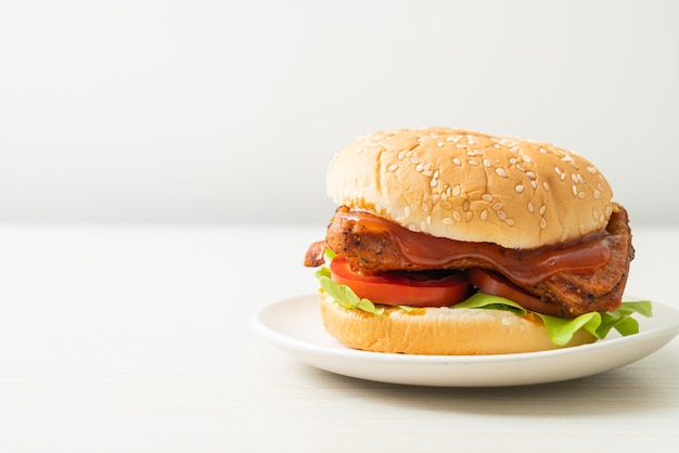 Gegrilde kipburger met saus op witte plaat