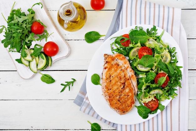 Gegrilde kipfilet en verse groentesalade - tomaten, komkommers en slabladeren. kip salade. gezond eten. plat leggen.