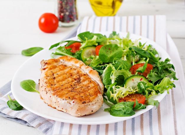 Gegrilde kipfilet en verse groentesalade - tomaten, komkommers en slabladeren. kip salade. gezond eten.