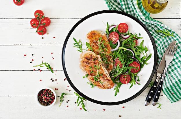 Gegrilde kipfilet en verse groentesalade van tomaten, rode ui en rucola.