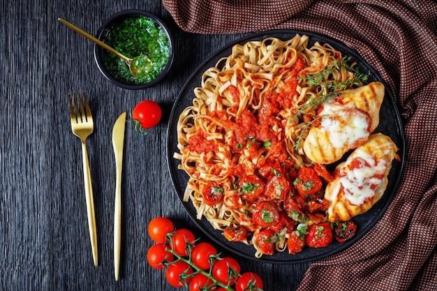 Gegrilde kipfilet met champignon linguine met tomatensaus, gebakken cherrytomaatjes gegarneerd met knoflooksaus, geserveerd met tijm op een zwarte plaat op een houten tafel, bovenaanzicht, plat leggen