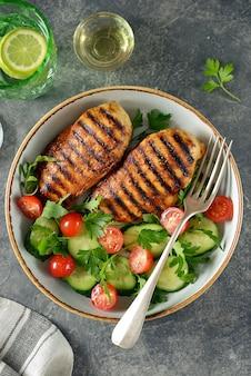 Gegrilde kipfilet met een salade van cherrytomaatjes, komkommers, rucola en peterselie