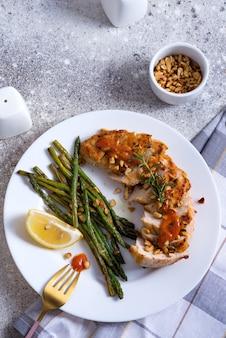 Gegrilde kipfilet met gegrilde asperges en schijfje citroen op steen. paleo dieet. concept voor een smakelijke en gezonde maaltijd.
