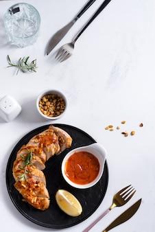 Gegrilde kipfilet met saus, pinda's en citroen op een bord