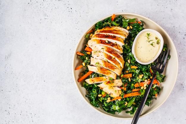 Gegrilde kipfilet salade met boerenkool, pijnboompitten en caesar dressing in een witte plaat.