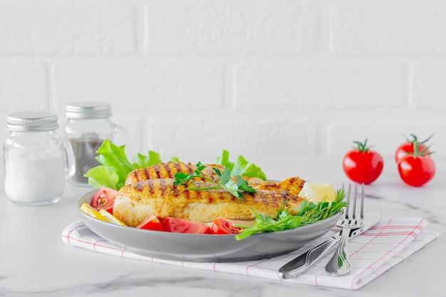 Gegrilde kipfilets geserveerd op een bord met salade en groenten. dieetvoeding.