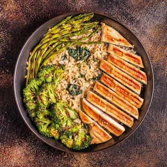 Gegrilde kippenborst met bruine rijst, spinazie, broccoli, asperges, concept van dieet, gezond eten.