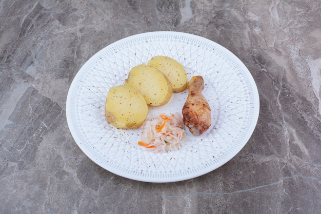 Gegrilde kippenpoot, aardappel en zuurkool op witte plaat.