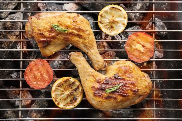 Gegrilde kippenpoot boven vlammen op een barbecue