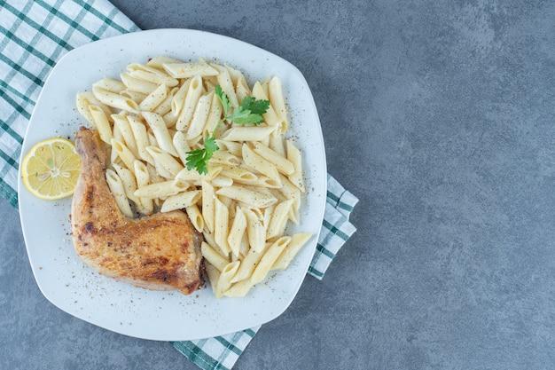Gegrilde kippenpoot en penne pasta op witte plaat.