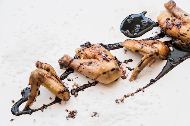 Gegrilde kippenpoten en kippenvleugels bedekt met sojasaus