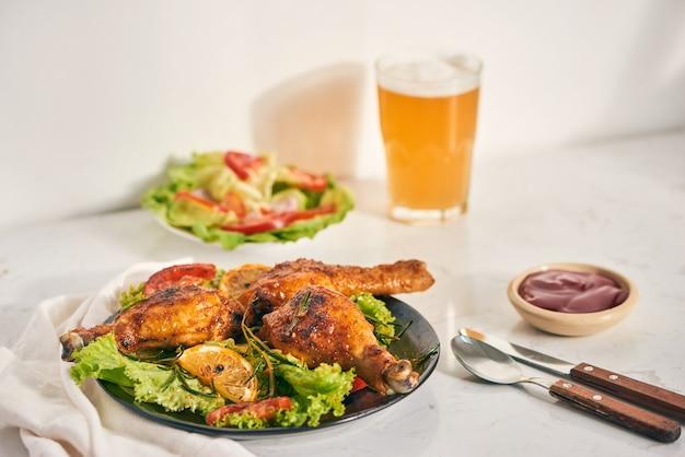 Gegrilde kippenpoten geroosterd op de grill op donkere plaat met tomatensaus in een kom en slabladeren, glazen mok bier