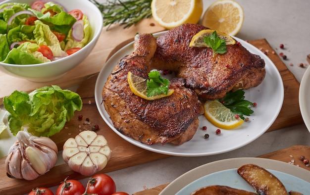 Gegrilde kippenpoten in barbecuesaus en geroosterde groenten en gemengde groentesalade met tomaten, citroen in witte plaat op lichte kleurenstenen tafel.