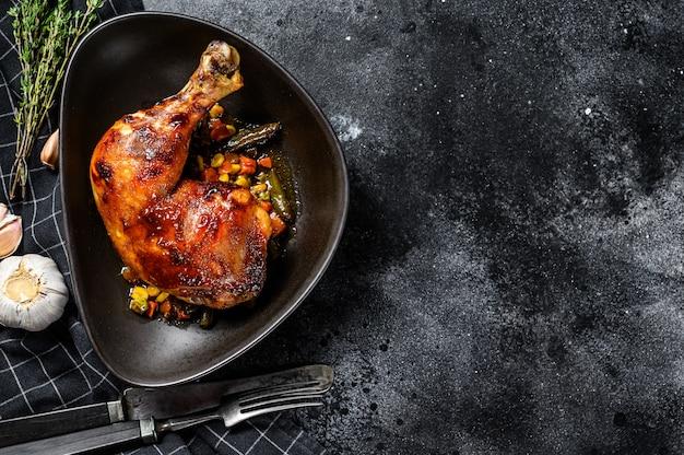 Gegrilde kippenpoten met kruiden en knoflook. zwarte achtergrond. bovenaanzicht. kopieer ruimte