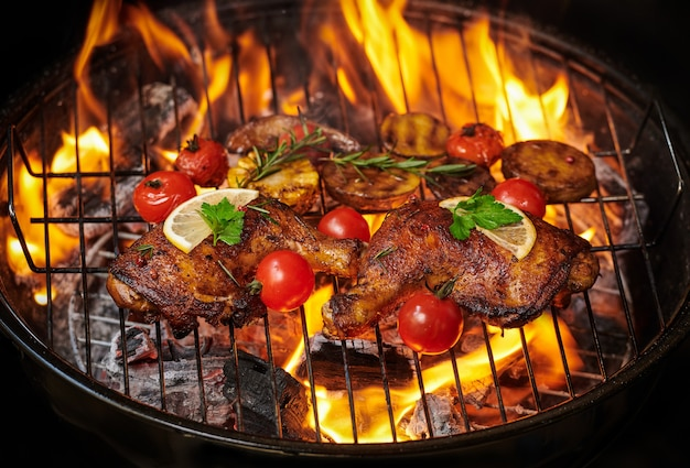 Gegrilde kippenpoten op de vlammende grill met gegrilde groenten met tomaten, aardappelen, peperzaadjes, zout.