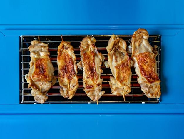 Gegrilde kippenstick op het effen blauwe elektrische fornuis van bovenaf voor eenvoudige en minimale voedselachtergrond