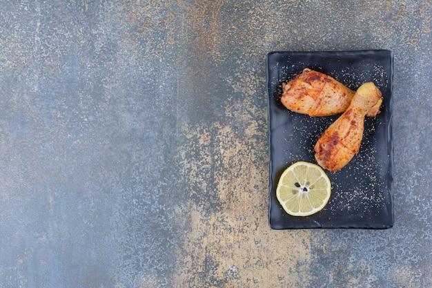 Gegrilde kippentrommelstokken op zwarte plaat met citroen.
