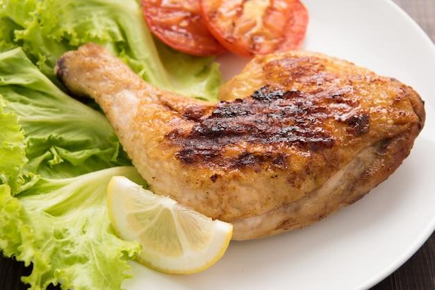 Gegrilde kippenvertraging en groente op witte schotel