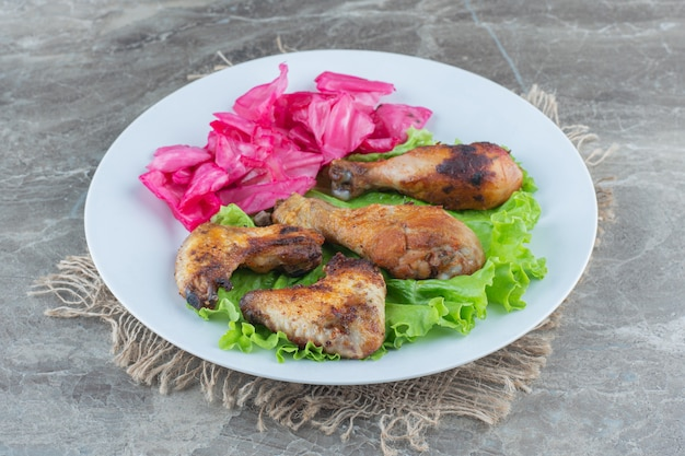 Gegrilde kippenvlees en augurk met slablad op witte plaat.