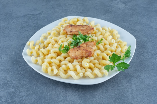 Gegrilde kippenvleugels bovenop gekookte pasta.