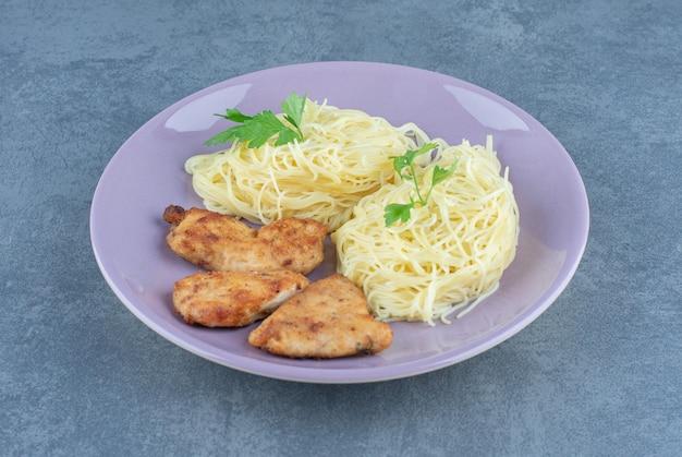 Gegrilde kippenvleugels en spaghetti op paarse plaat.