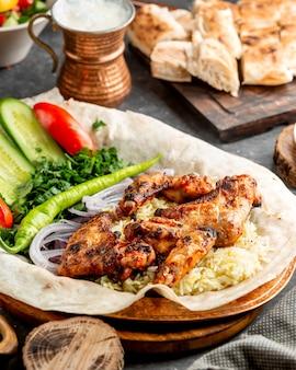 Gegrilde kippenvleugels geserveerd met rijst en salade