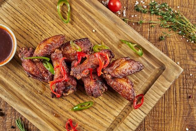 Gegrilde kippenvleugels in honing en bier saus geserveerd in een op een houten bord met kruiden. close-up, selectieve aandacht.