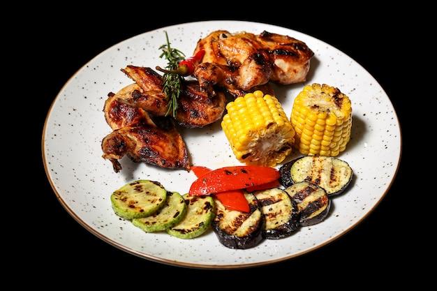 Gegrilde kippenvleugels met groenten op zwart