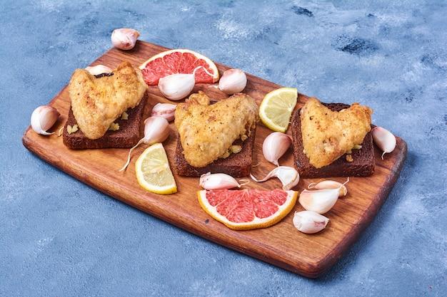 Gegrilde kippenvleugels met kruiden op een houten bord op blauw