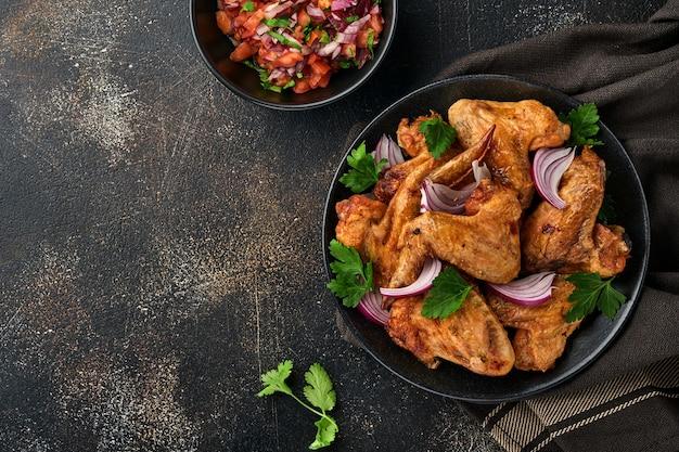 Gegrilde kippenvleugels of geroosterde bbq met kruiden en tomatensalsasaus op een zwarte plaat