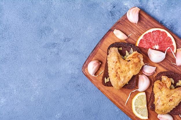 Gegrilde kippenvleugels op een houten bord op blauw