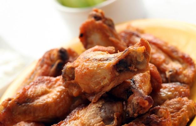 Gegrilde kippenvleugels op een witte tafel