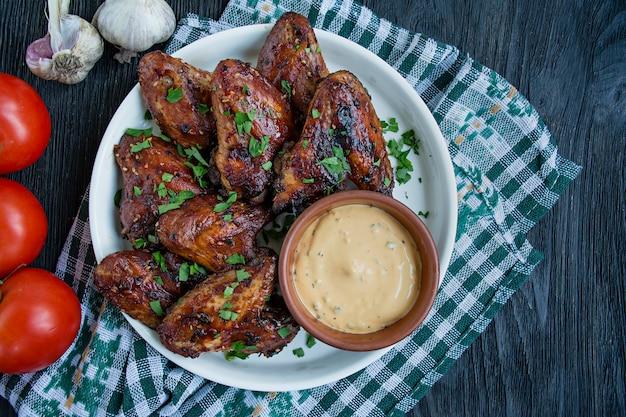 Gegrilde kippenvleugeltjes met saus en kruiden. gebakken kippenvleugeltjes in de pan.