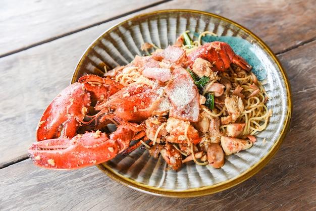 Gegrilde kreeft spaghetti worst ham groenten en kaas zeevruchten op houten tafel