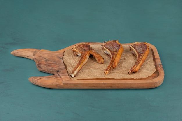 Gegrilde lamskoteletjes met op een houten bord.