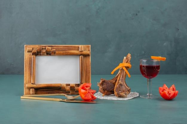 Gegrilde lamskoteletten, fotolijst en glas wijn op blauwe tafel.
