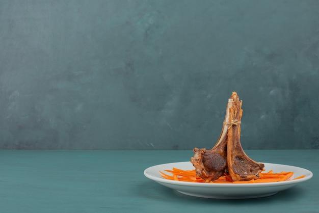 Gegrilde lamskoteletten op een witte plaat met plakjes wortel.