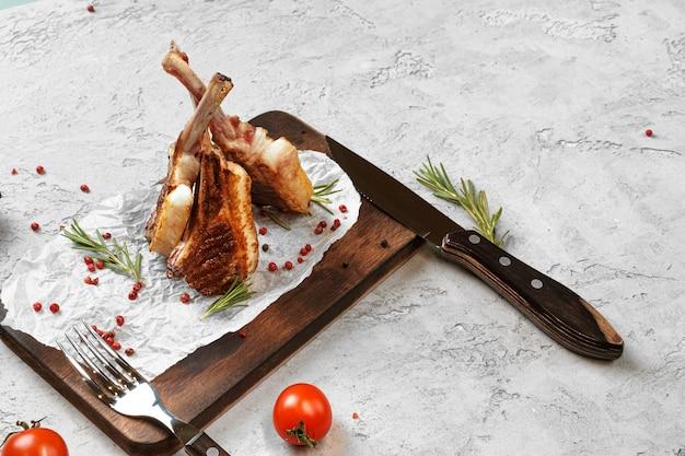 Gegrilde lamsrack geserveerd op een houten bord. lamssteaks