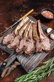 Gegrilde lamsschaap ribs chops steaks op een houten bord. donkere achtergrond. bovenaanzicht.