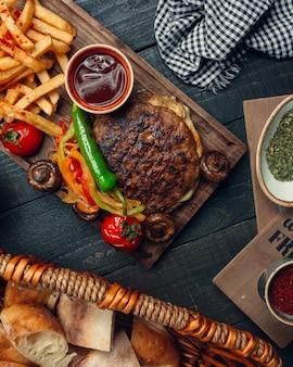 Gegrilde lamsvleesloze hamburger geserveerd met geroosterde paprika, friet, champignon, ketchup